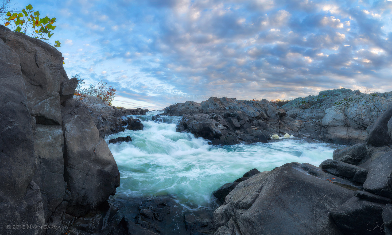 panorama showcases the huge rocks beneath a dramatic, autumn sunrise at Great Falls National Park, Virginia.