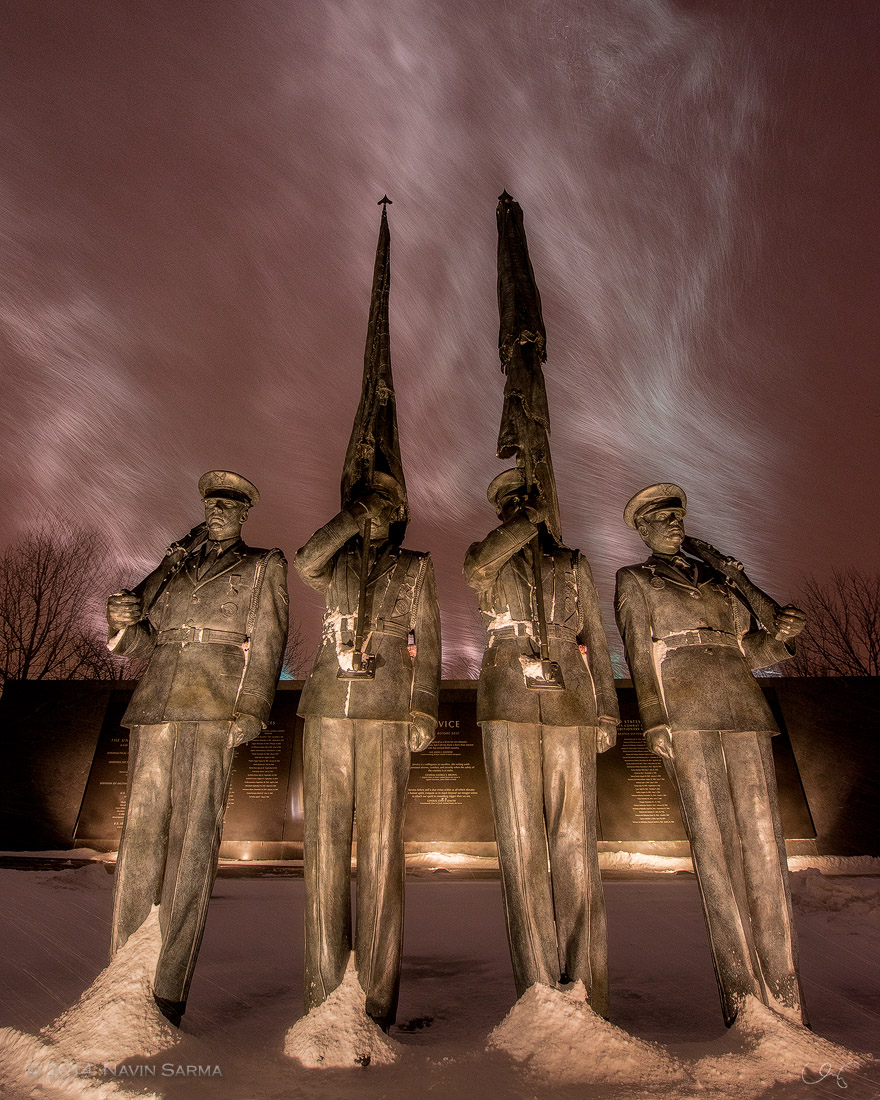 A vertical version: snow and wind mix in with the orange city glow of night at the Air Force Memorial.