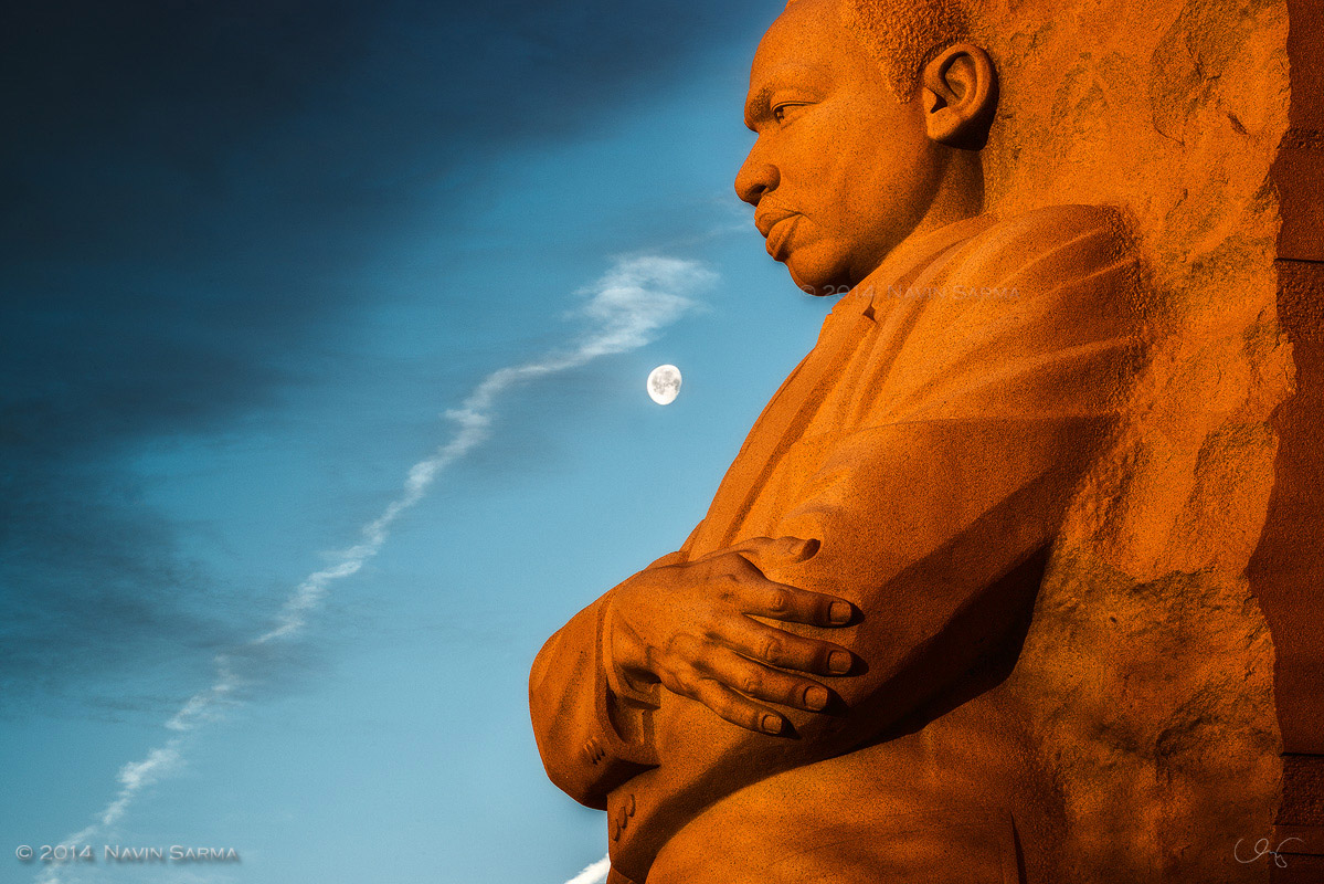 Sunlight bathes the Martin Luther King Memorial in contrast to blue skies and the Moon