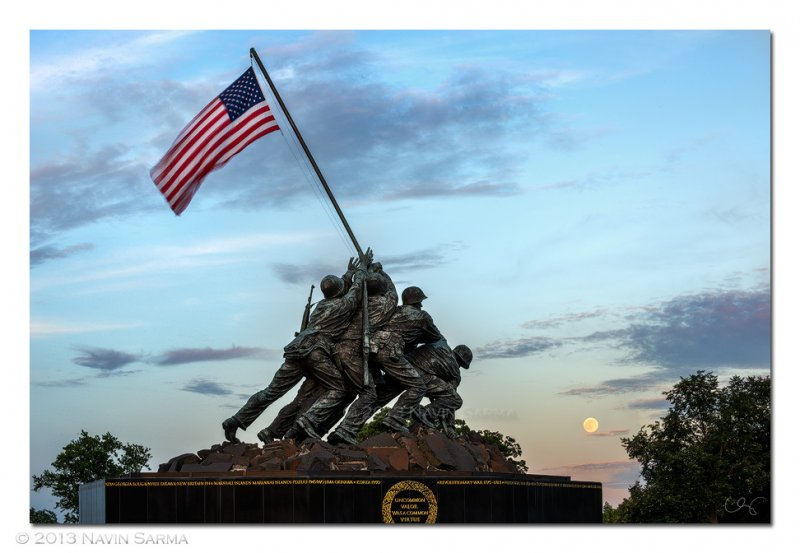 The super full moon rises over a colorful sunset at the Iwo Jima Memorial.