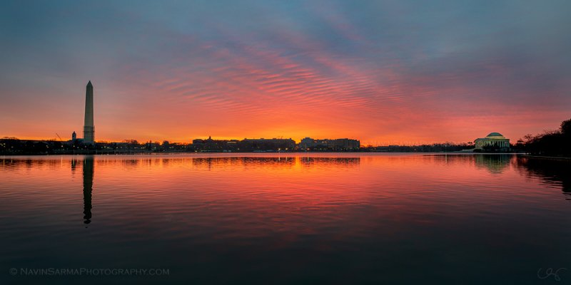 The Washington Monument and the Jefferson Memorial surround a brilliant orange and pink sunrise at the Tidal Basin