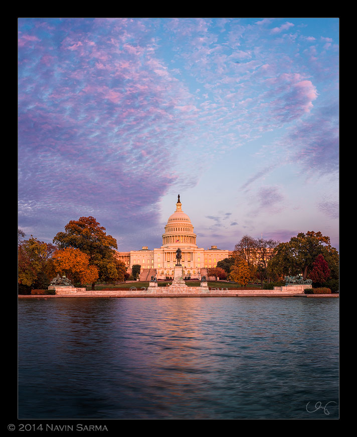Brilliant pink hues emerge over peak fall foliage the the U.S. Capitol