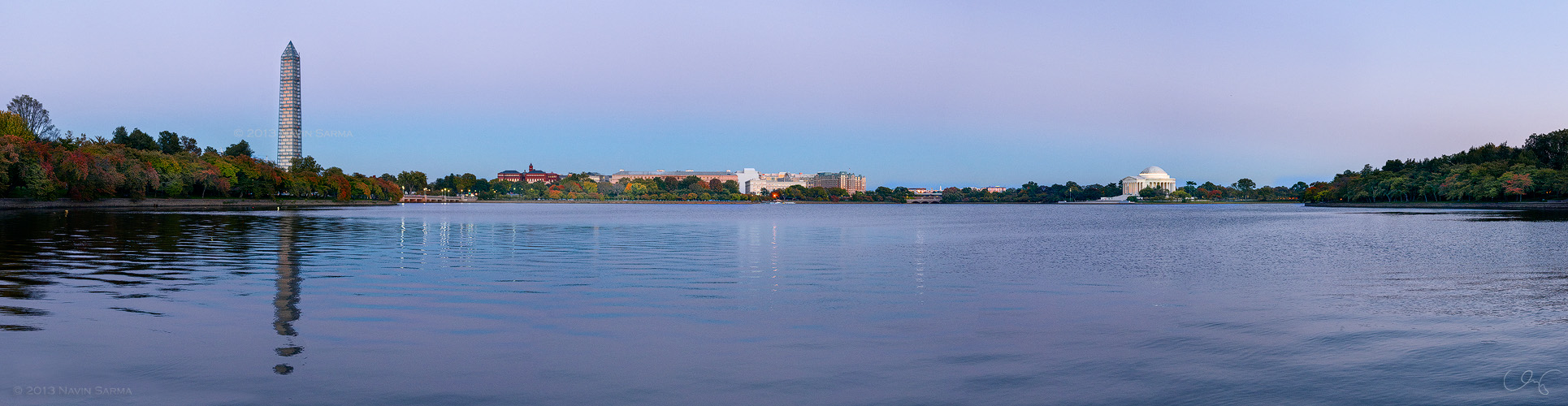 During a blue and pink sunset, fall colors start to turn at Washington, D.C.'s Tidal Basin in front of the Washington Monument and Jefferson Memorial.