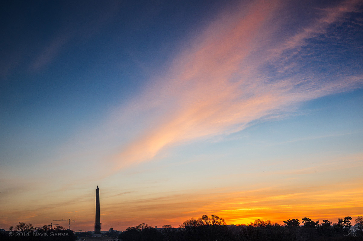 A silhouette of the Washington monument during sunrise from the Lincoln Memorial.