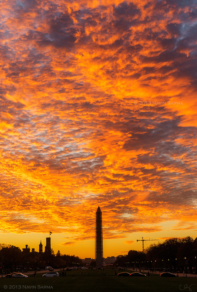 The Washington Monument's shape cuts into the bright, orange sunset sky.