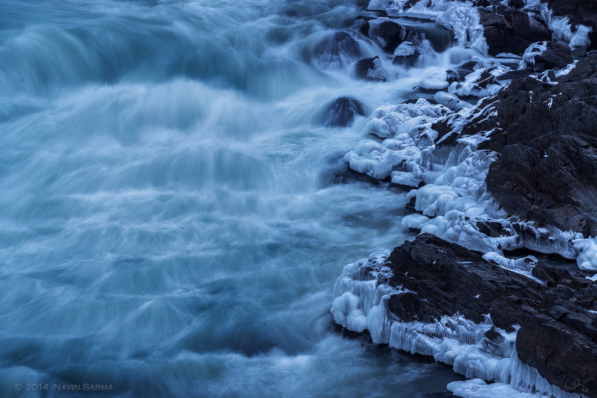 Flowing water contrasts the icy rocks of Great Falls