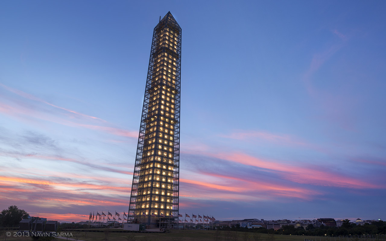 Radiant pink, orange, and blue color surrounds the newly lit Washington Monument